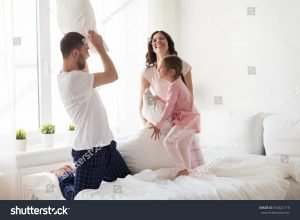 parents have a pillow fight with child