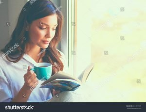 woman having hot drink and reading