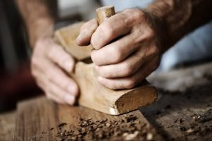 man cutting wood for window